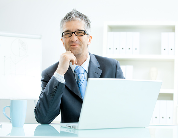 Smiling professional using laptop to choose his investments